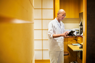 A chef in a small commercial kitchen, an itamae or master chef using a digital tablet.の写真素材 [FYI02255143]