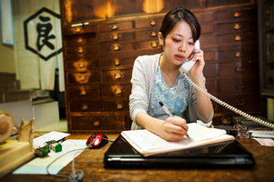 A small artisan producer of specialist treats, sweets called wagashi. A woman taking an order over tの写真素材 [FYI02255147]