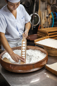 A small artisan producer of wagashi. A man mixing a large bowl of ingredients and pressing the mixedの写真素材 [FYI02255150]