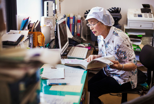 A mature woman at a desk in the office of a fast food unit and noodle production factory.の写真素材 [FYI02255158]