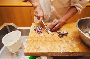 A chef working in a small commercial kitchen, an itamae or master chef slicing fish with a large kniの写真素材 [FYI02255162]