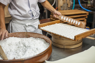 A small artisan producer of wagashi. A man mixing a large bowl of ingredients and pressing the mixedの写真素材 [FYI02255164]
