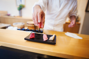 A chef working in a small commercial kitchen, an itamae or master chef presenting a fresh plate of sの写真素材 [FYI02255166]