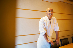 A chef , an itamae or master sushi chef wearing white jacket and apron.の写真素材 [FYI02255173]