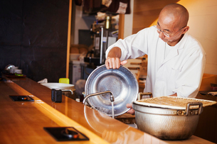 A chef working in a small commercial kitchen, an itamae or master chef making sushi.の写真素材 [FYI02255175]