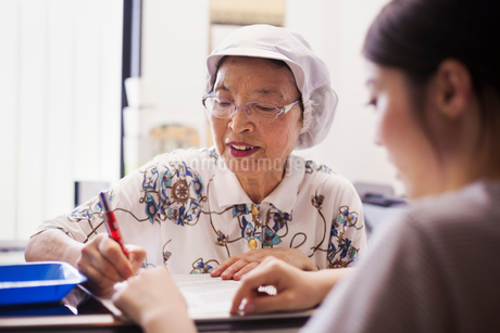 A mature woman at a desk in the office of a fast food unit and noodle production factory.の写真素材 [FYI02255176]