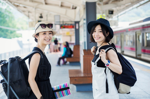 Two young women standing on a platform at a railway station.の写真素材 [FYI02255181]