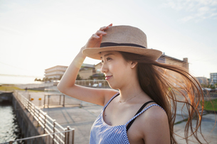Young woman standing on a pier by water holding her straw hat on her head.の写真素材 [FYI02255190]