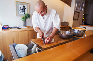 A chef working in a small commercial kitchen, an itamae or master chef slicing fish with a large kniの写真素材 [FYI02255191]