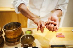 A chef working in a small commercial kitchen, an itamae or master chef pressing rice into shape forの写真素材 [FYI02255195]