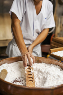 A small artisan producer of wagashi. A man mixing a large bowl of ingredients and pressing the mixedの写真素材 [FYI02255197]
