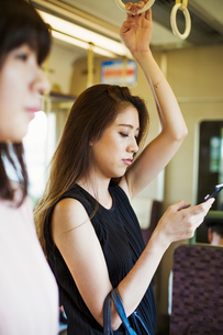 Woman with long brown hair traveling on public transport, using mobile phone.の写真素材 [FYI02255205]