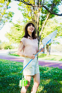 Young woman with long brown hair standing in a park, holding a butterfly net.の写真素材 [FYI02255207]