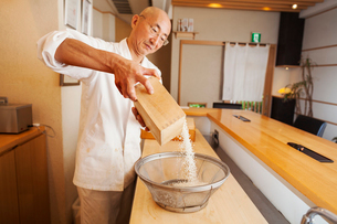 A chef working in a small commercial kitchen, an itamae or master sushi chef preparing rice for cookの写真素材 [FYI02255208]