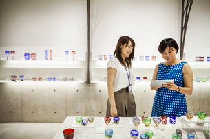 Saleswoman in a shop selling Edo Kiriko cut glass in Tokyo, Japan.の写真素材 [FYI02255211]
