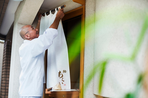 A chef in a small commercial kitchen, an itamae or master chef drawing a curtain across a door.の写真素材 [FYI02255212]