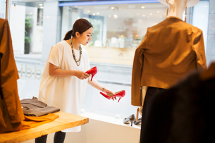 Woman working in a fashion boutique in Tokyo, Japan, holding a pair of red high heels.の写真素材 [FYI02255214]