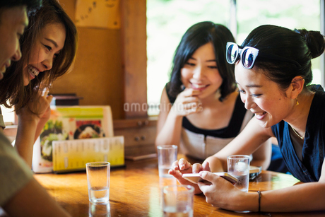 Three young women and a man sitting in a cafe.の写真素材 [FYI02255220]