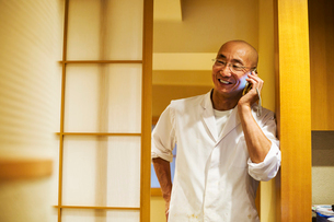 A chef  in a small commercial kitchen, an itamae or master chef on his smart phone.の写真素材 [FYI02255223]