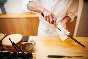 A chef working in a small commercial kitchen, an itamae or master chef preparing to make sushi, cleaの写真素材 [FYI02255233]