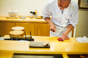 A chef working in a small commercial kitchen, an itamae or master chef slicing fish with a large kniの写真素材 [FYI02255234]