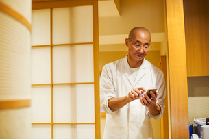 A chef in a small commercial kitchen, an itamae or master chef using a smart phone.の写真素材 [FYI02255236]