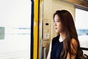 Woman with long brown hair traveling on public transport.の写真素材 [FYI02255237]