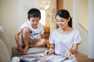 Family home. A woman and her son looking at a photographic album.の写真素材 [FYI02255244]