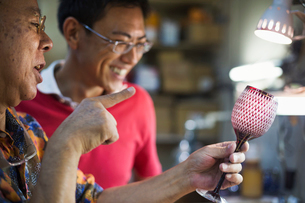 Two people, a father and son at work in a glass maker's studio workshop, inspecting a red cut glassの写真素材 [FYI02255249]