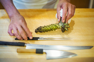 A chef working in a small commercial kitchen, an itamae or master chef grating horseradish root forの写真素材 [FYI02255250]