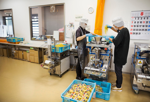 Workers in a factory producing Soba noodles . Two men mixing noodle dough in a machine.の写真素材 [FYI02255254]