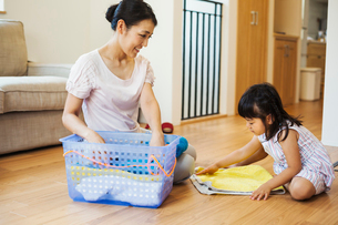Family home. A woman and her daughter folding clean laundry.の写真素材 [FYI02255262]