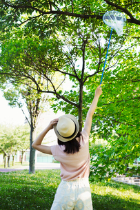 Rear view of a young woman with long brown hair standing in a park, holding a butterfly net.の写真素材 [FYI02255264]