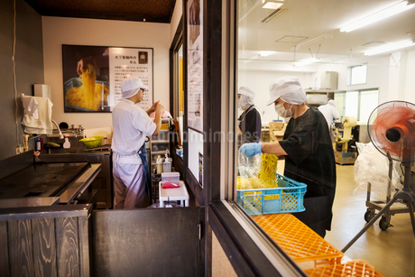 View of the noodle factory production unit from a commercial  kitchen serving a noodle shop. Peopleの写真素材 [FYI02255287]