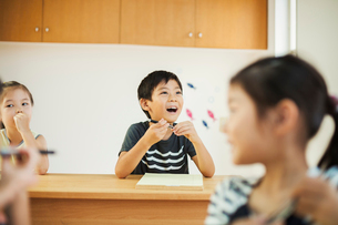 Three children, a boy and two girls in a classroom.の写真素材 [FYI02255301]