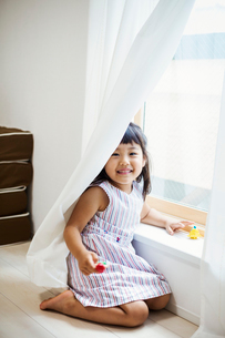 Family home. A girl playing by a window, hiding behind the net curtain.の写真素材 [FYI02255313]