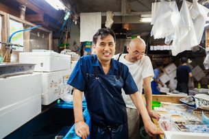 A traditional fresh fish market in Tokyo. Two men in aprons working on a fresh produce stall.の写真素材 [FYI02255317]