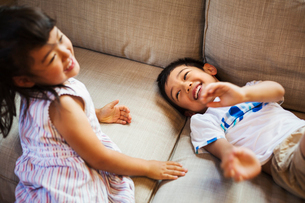 Family home. Two children playing on the floor, giggling.の写真素材 [FYI02255318]