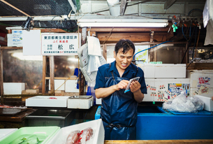 A traditional fresh fish market in Tokyo. A man in a blue apron standing behind the counter of his sの写真素材 [FYI02255321]