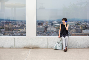 A woman seated by a window with a view over a large city with her back to the view, making a call onの写真素材 [FYI02255330]