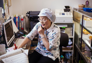 A mature woman at a desk in the office of a noodle production factory on the telephone.の写真素材 [FYI02255336]