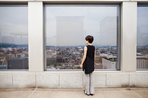 A woman standing looking over a city from a high viewing point.の写真素材 [FYI02255340]