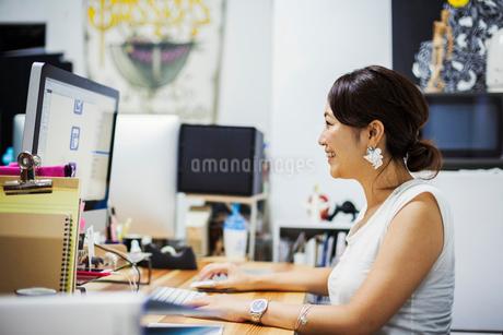 Design Studio. A woman sitting at a desk using a computer.の写真素材 [FYI02255348]