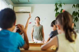 A group of children in a classroom, one with her hand up ready to answer a question.の写真素材 [FYI02255363]