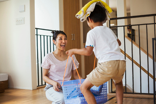 Family home. A woman and her son sorting the laundry, the boy balancing towels on his head.の写真素材 [FYI02255364]