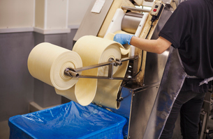 A Soba noodle factory.  Sheets of fresh noodle dough being passed through a large pressing machine.の写真素材 [FYI02255369]