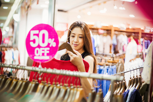 Young woman with long brown hair in a clothes shop.の写真素材 [FYI02255376]