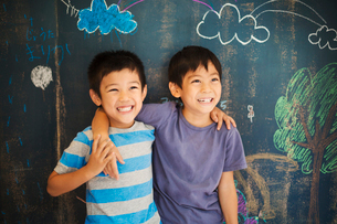 Children in school. Two boys standing with their arms around each other's shoulders by a chalkboard.の写真素材 [FYI02255377]