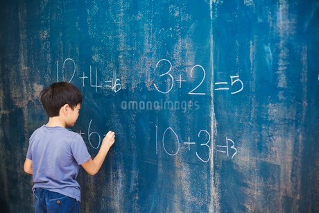 A group of children in school. A boy writing in chalk on a chalkboard.の写真素材 [FYI02255383]
