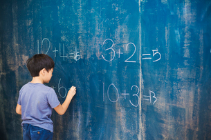 A group of children in school. A boy writing in chalk on a chalkboard.の写真素材 [FYI02255383]